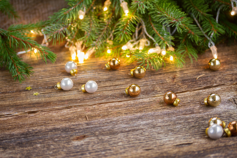 christmas background  - wooden table with defocused lights and glass decorationd